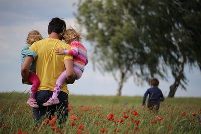 Padre con niños paseando por el prado